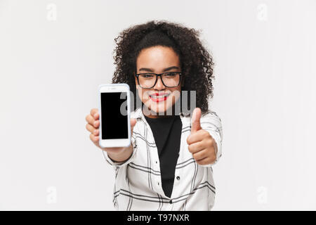 Portrait of an african woman standing isolated over white background, showing blank screen mobile phone, thumbs up - Stock Image