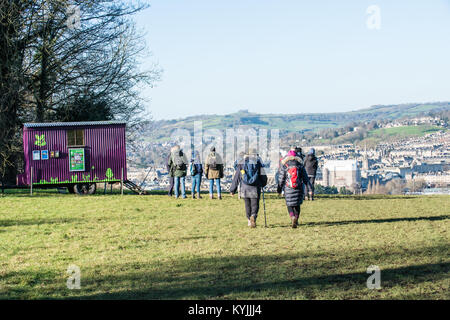 A group of walkers on a winter ramble across Bath's beautiful Skyline walking past a National Trust sign - Stock Image