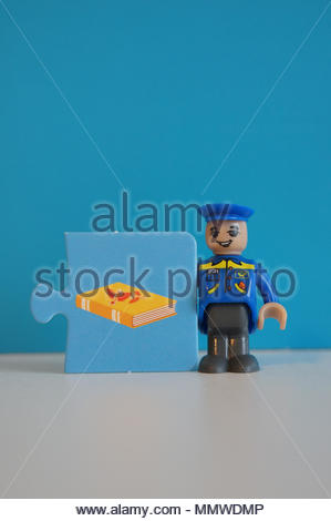 Playtive toy mailman standing next to a puzzle piece with book illustration - Stock Image