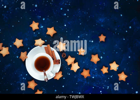 Astronomy and constellation flat lay with copy space. Teatime with star-shaped cookies. White porcelain cups on a starry sky background. - Stock Image