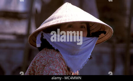 A young Vietnamese woman wearing a traditional, conical straw hat. - Stock Image