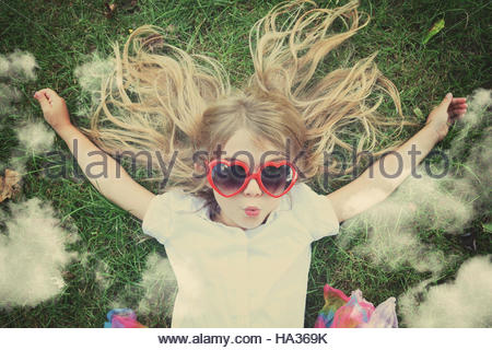 A happy child is laying down on the green grass looking up at imaginary clouds for a freedom, imagination or lifestyle - Stock Image