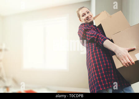 moving into a new house - smiling young woman carrying boxes. copy space - Stock Image