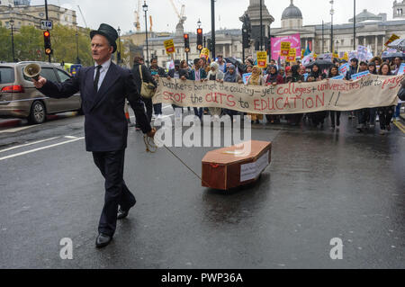 London, UK. 17th October 2018. A man in a black top hat rings a bell and pulls a coffin as staff and students from Further Education Colleges across the country march from Waterloo Place to to a rally in Parliament Square calling for the vital work that FE Colleges do to be recognised and properly funded. The #Loveourcolleges action called for funding to allow the colleges to do their job properly and to pay teachers on comparable rates to their colleagues in schools and Higher Education. Credit: Peter Marshall/Alamy Live News - Stock Image
