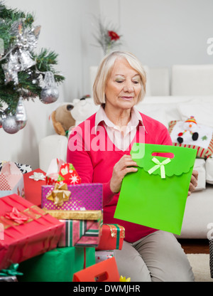 Woman Holding Bag While Sitting By Christmas Presents - Stock Image