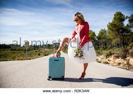 A woman dressed as a bride, with a red jacket, a bouquet and a leg resting on a suitcase, poses in the middle of a lonely road. - Stock Image