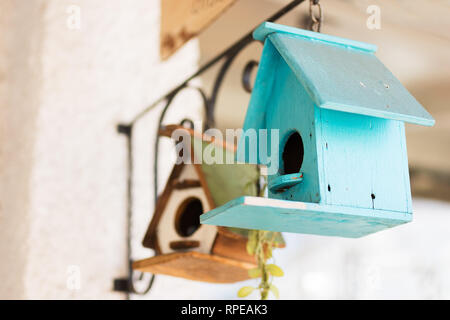 Two home made small bird houses hanging from the side of a house. - Stock Image