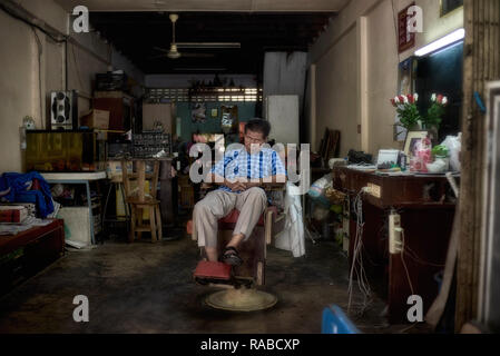 Man asleep in a chair. Thailand barber sleeping on a quiet day at his shop. Southeast Asia - Stock Image