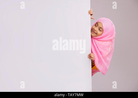 young Muslim girl with hijab peeking from behind the wall and smiling - Stock Image