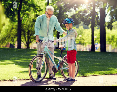 grandfather and boy with bicycle at summer park - Stock Image