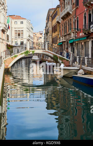 Boats docked in small canal in Venice, Italy - Stock Image