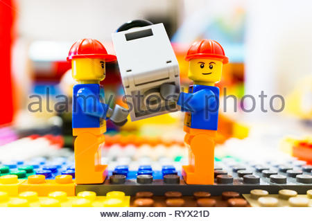 Poznan, Poland - March 14, 2019: Two Lego construction workers carry together a safe. - Stock Image