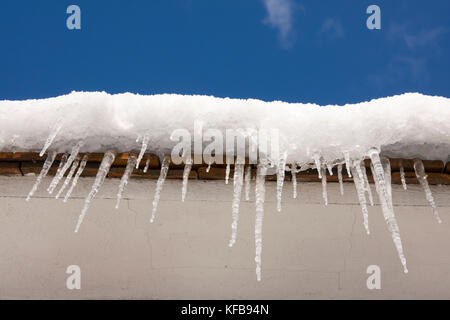 icicles on roof of house - Stock Image