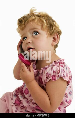 Child listening to a pink mobile phone      Ref: CRB538_103609_0003  COMPULSORY CREDIT: Martin Harvey / Photoshot - Stock Image
