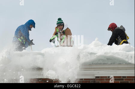 Lexington, MA, USA, 21 Feb, 2015.  Contractors clearing snow from the roof of a three story apartment building in - Stock Image