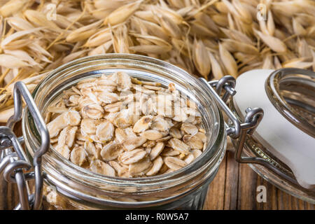 Glass jar full of oat flakes. Common oats. Avena sativa. Organic rolled oats. Healthy nutrients, dietary fiber. Brown wooden board. Dry cereal grains. - Stock Image