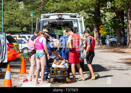 A near drowned man saved by surf rescue volunteers helped into a NSW Ambulance on a stretcher at Palm Beach,Sydney,Australia - Stock Image