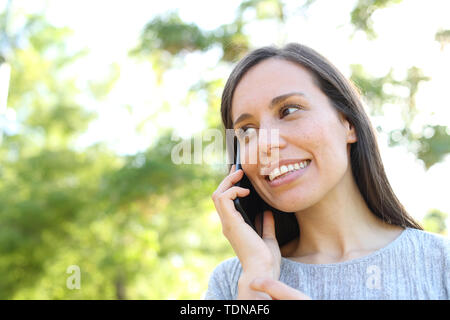 Happy woman talks on smart phone standing outdoors in a park - Stock Image