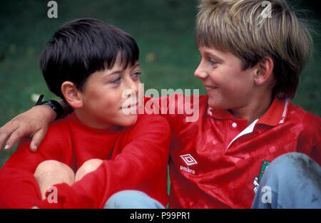 two young boys chatting on football field - Stock Image