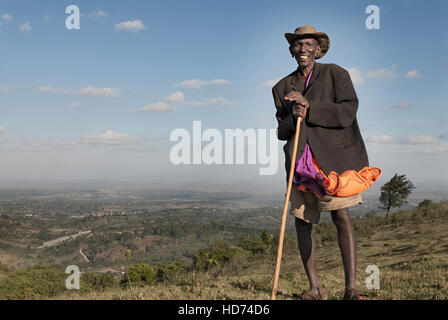 A Maasai elder man smiles on top of a hill overlooking Kenya. Africa. - Stock Image
