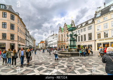 Tourists wander the Stroget shopping district near the Stork Fountain, the longest pedestrian street in the world, in Copenhagen, Denmark. - Stock Image