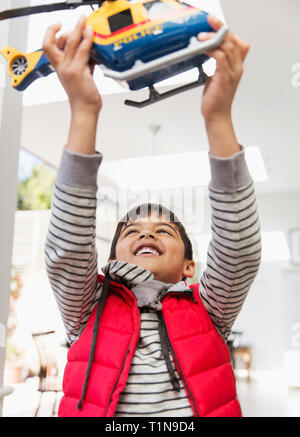 Happy boy playing with toy helicopter - Stock Image