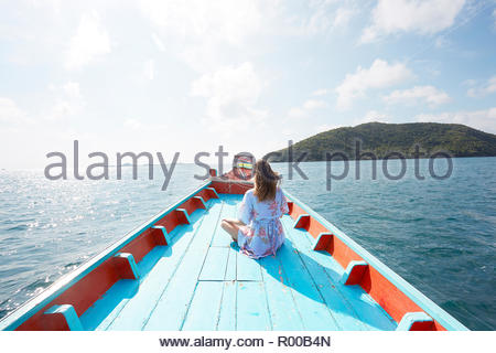 Young woman sitting on blue boat - Stock Image