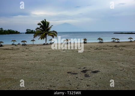A view of Mount Cameroon from across the sea from Bioko Island, Equatorial Guinea, with a beach, palm trees and sun loungers in the foreground - Stock Image