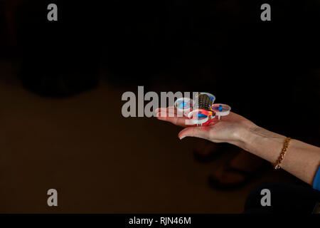 A woman's hand and arm holding an active EACHINE e10 mini quadcopter drone. - Stock Image