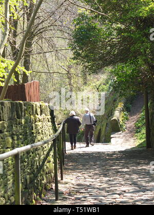 Elderly couple descending 'The Buttress', Hebden Bridge - a steep cobbled footpath leading from the Calderdale town to the village of Heptonstall - Stock Image