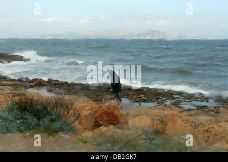 Despite stormy weather a person takes a walk at the agitated bay of Alcudia on Majorca, Spain, 18 October 2007. - Stock Image