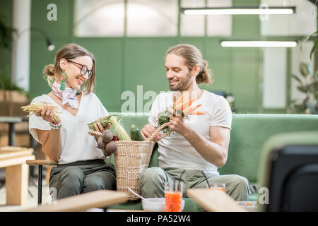 Young vegetarian couple sitting on the sofa with bag full of fresh vegetables in the beautiful green home interior - Stock Image