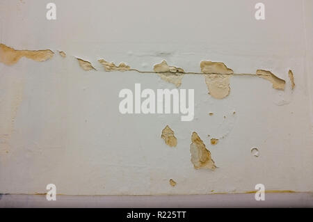 Cracked damaged paint on a wall. - Stock Image