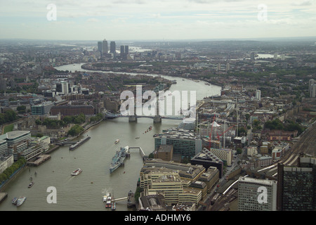 Aerial photograph of Tower Bridge over the River Thames in London with views to Wapping, Rotherhithe, Canary Wharf & the estuary - Stock Image