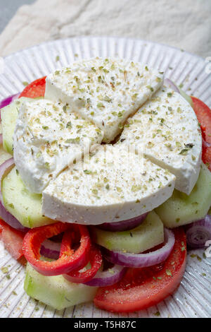 Traditional greek salad made with fresh cucumber, tomato, paprika, red onion, kalamata olives, white salted feta cheese with oregano, close up - Stock Image