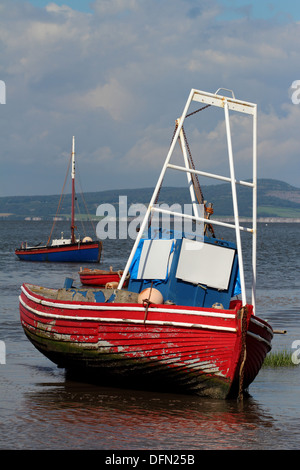 An old red and blue fishing boat on the beach of Morecambe Bay at low tide - Stock Image