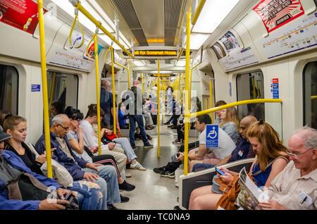 Passengers on a London Underground train. - Stock Image