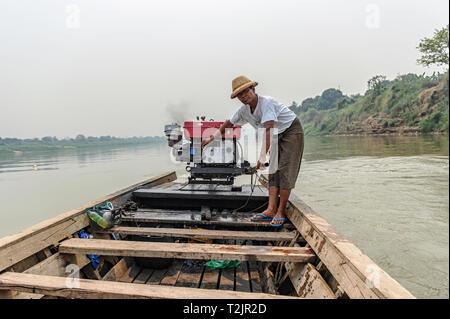 River boatman transporting goods and people on the Myitnge River, near Inn Wa, Sagaing Region, Myanmar (Burma) - Stock Image