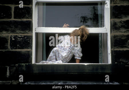 little girl in nightie climbing out of sash window of old house - Stock Image