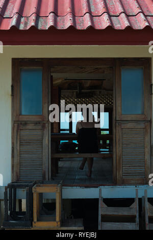Girl through the window of Lighthouse restaurant, Phangan island, Thailand - Stock Image