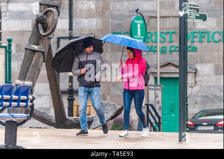 Bantry, West Cork, Ireland. 14th Apr, 2019. Two people walk in the rain in Bantry this afternoon.  County Cork is currently in the midst of a Status Yellow Rainfall and Wind Warning which lasts until 6pm Monday. Credit: Andy Gibson/Alamy Live News. - Stock Image