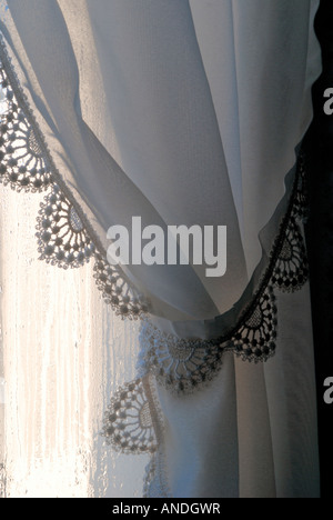 Net window curtain with swag, France. - Stock Image