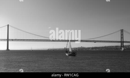 Sailboats with white sails on the Tagus River, 25 of April Bridge, Lisbon, Portugal - monochrome. - Stock Image