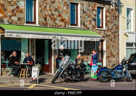Schull, West Cork, Ireland. 15th Oct, 2018. Tourists and locals make the most of the sunny weather and sit outside a local café to consume their teas and coffees. The day will remain sunny with unsettled weather forecast for the rest of the week.  Credit: Andy Gibson/Alamy Live News. - Stock Image