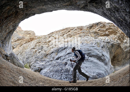 Hiker exploring rock formations, Marble Canyon, Death Valley National Park, California - Stock Image