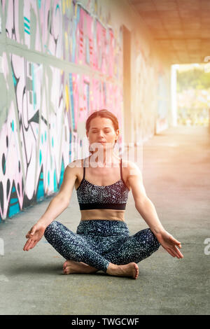 woman sitting meditating, practicing yoga in a building with graffiti and concrete walls. - Stock Image