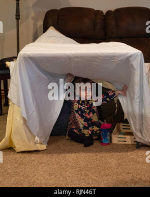 A Caucasian girl toddler plays under a makeshift tent made from a sheet draped over furniture. - Stock Image