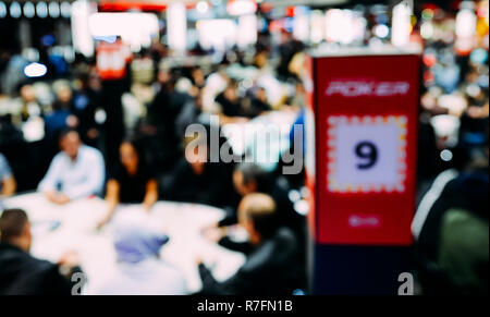Deliberately defocused view of large multi table poker tournament. Players sitting at table and dealers dealing cards. Large field tournament - Stock Image