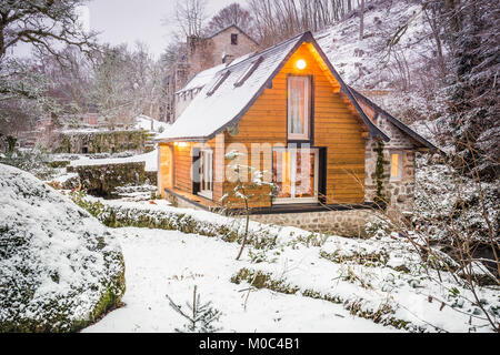 Exterior of a small holiday home in a snow covered landscape in France - Stock Image
