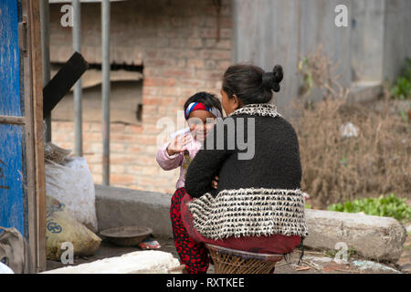 A young Nepali girl smiles and waves as she is held by her mother. Bhaktapur, Nepal. - Stock Image